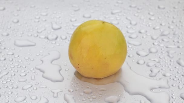Rotation, drops of water fall on a ripe yellow apricot.