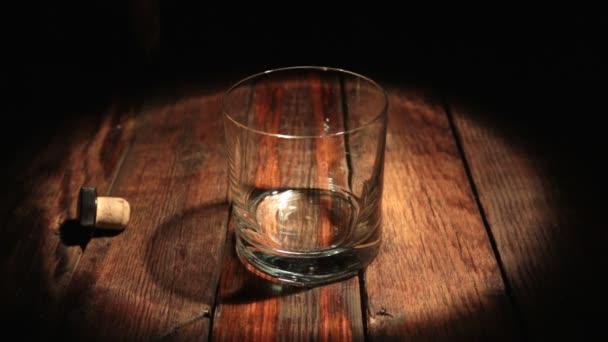 Szakadó whisky a palackból, fekete háttér, a távolsági fény. Pohár rum alkohol.