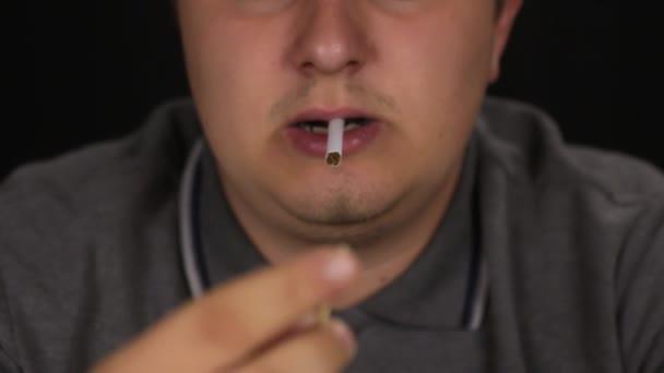 Man lights a cigarette using a wooden match.