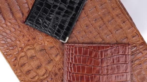 Rotace, close-up dva pasy, ležící na hnědé Krokodýlí kůže.