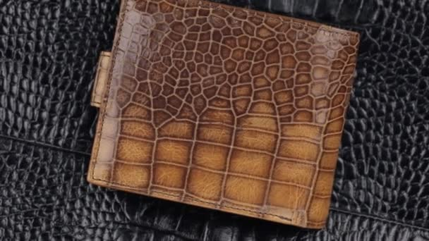 Close-up. Rotation of beautiful male wallet lying on a black leather.