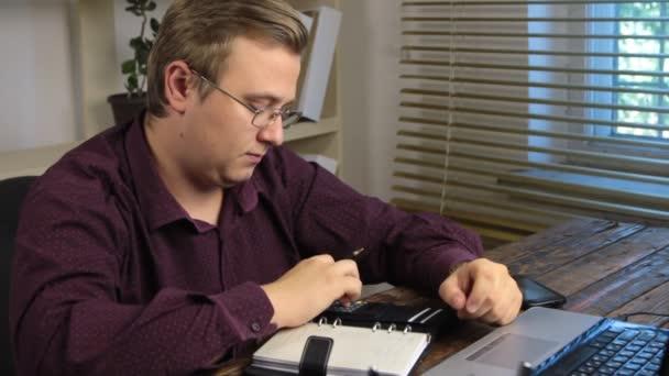 Podnikatel výpočtu na kalkulačce a zapíše si částku v poznámkovém bloku. Kancelářská práce