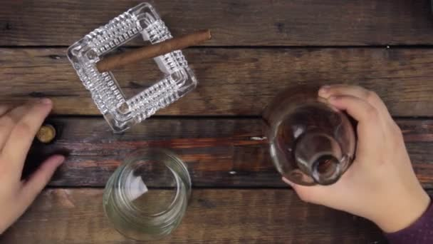 Člověk bere alkohol láhev a nalijte do sklenice.