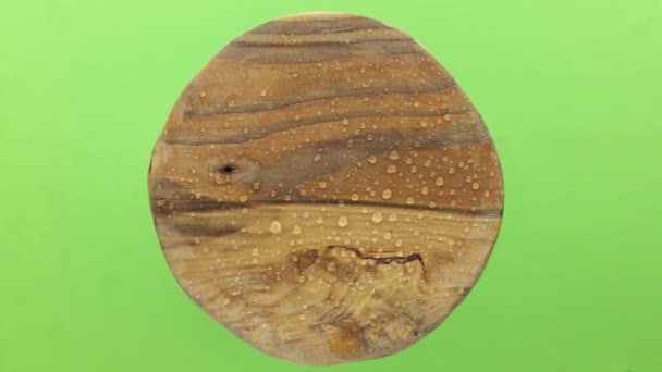 Raindrops falling on an old round wooden plank. Isolated on green background