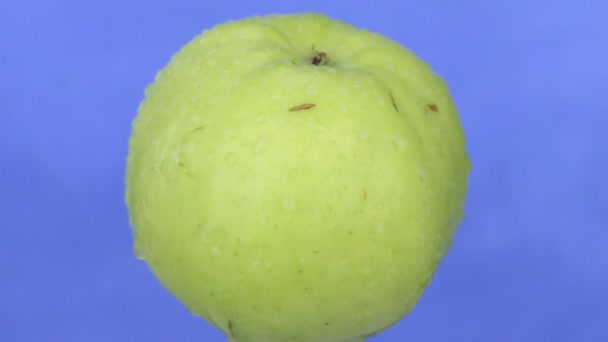 Rotace zelené jablko v kapky vody. Detail. Izolovaný