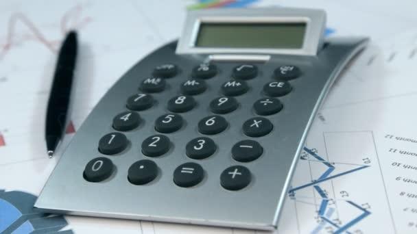 Rotace Kalkulačka a perem ležící na grafech. Finanční analýza