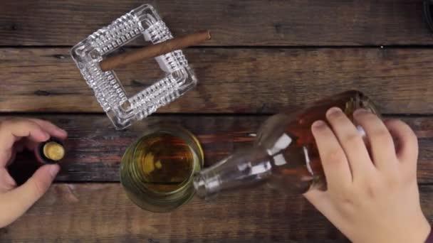 Az ember vesz egy üveg, és öntsük alkohol egy poharat. Szemközti nézet