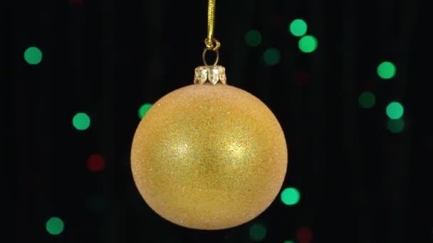 Vánoční ozdoby, koule, visí na pozadí blikající světla.