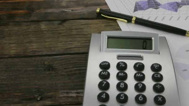 Office desk with business charts, glasses, pen and calculator. Slider shot.