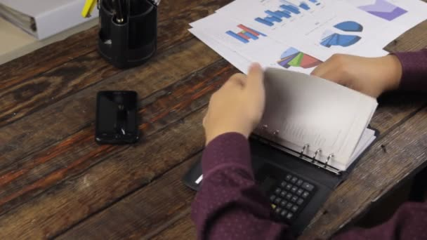 Businessman analyzes charts and writes in a notepad.