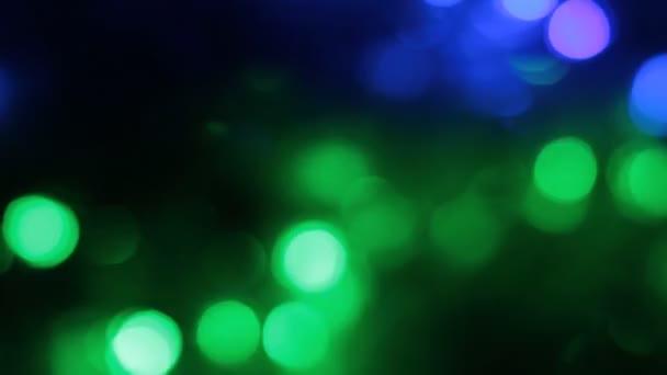 Rotace bokeh, garland, blikající světla na černém pozadí. Vánoční pozadí