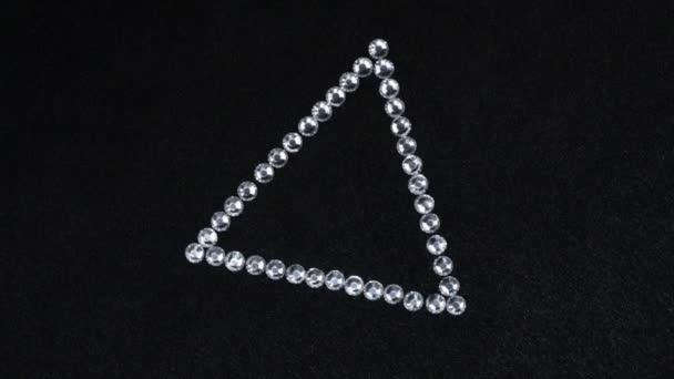 Drehung eines Dreiecks aus silbernen Strasssteinen auf schwarzem Stoff, das Dreieck symbolisiert die Fertigstellung.