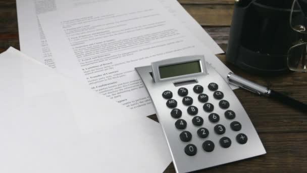 Slider shot. Contract, calculator, pen and chart.