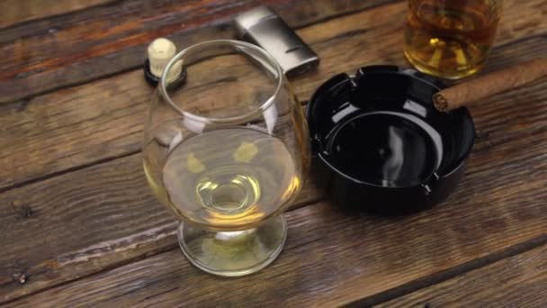 Csúszka lövés. Egy szivar egy hamutartó, és egy pohár alkoholt a régi asztalra.