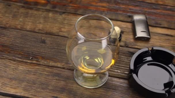 Panoráma. Egy szivar egy hamutartó, és egy pohár alkoholt a régi asztalra.