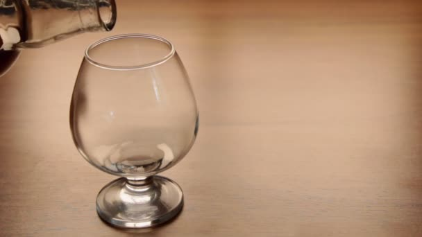 Öntés konyak palackból üvegbe az asztalra