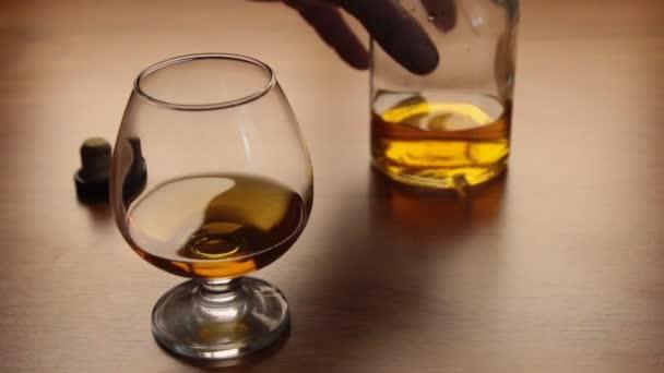 Öntsön Cognac palackból üvegbe az asztalra
