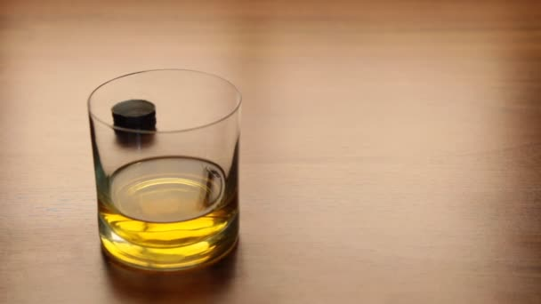 Pour whiskey from bottle into glass on table