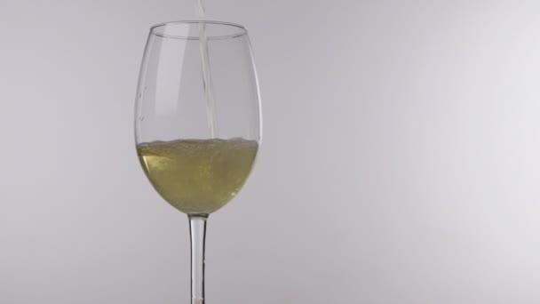 Nalévání bílého vína z láhve do skla na bílém pozadí, uzavření.