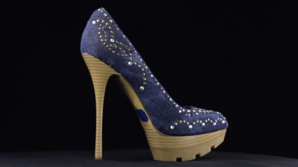 Rotation, shoes with high heels. Denim with rhinestones high heel shoes on black background.