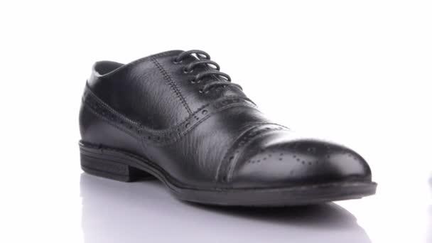A stílusos klasszikus fekete cipő fehér alapon történő elforgatása.