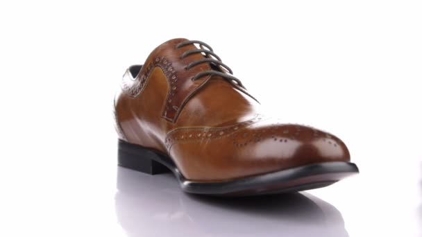 Rotation of a stylish classic brown shoe with laces on a white background.