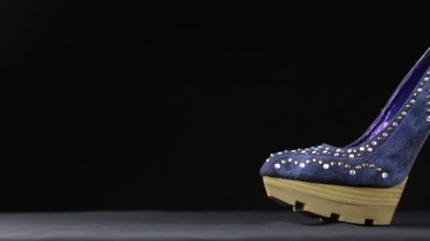 Blue womens high-heel shoes against black background. Slider shot.
