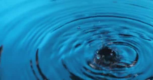 Panorama kapek vody padajících do modré vody. Krásná kruhová vlna, vlnka.