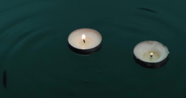 Kapky padají do zelené vody s plovoucími svíčkami. Svíčky plují na vlnách vody.