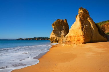 beautiful Algarve beach Praia da Rocha in Portugal, on a sunny cloudless day, no people on the beach, spotless blue sky, yellow sand and bright rocks