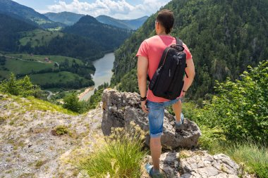 Man tourist with backpack standing on mountain and look on Spajici lake and hills from the high in Tara national park in Zaovine, Serbia