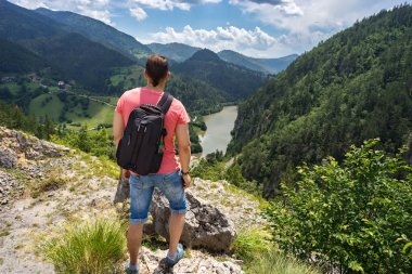 Man traveller with backpack standing on mountain and look on Spajici lake and hills from the high in Tara national park in Zaovine, Serbia