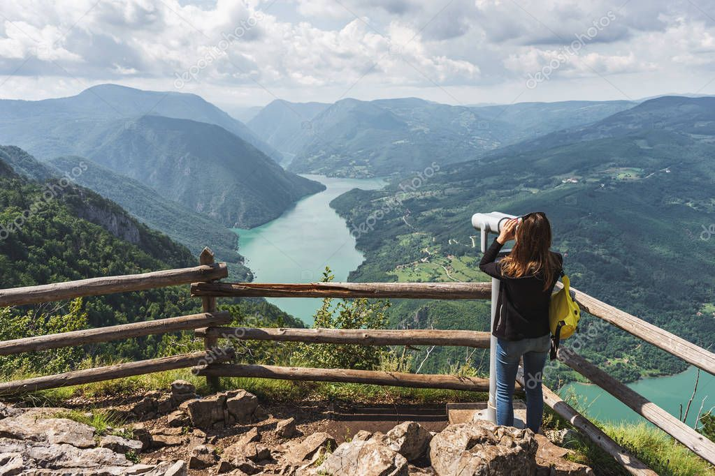 A tourist girl looks at the beautiful nature through a stationary binoscope at the observation point of Banjska Stena in the Tara National Park in Serbia