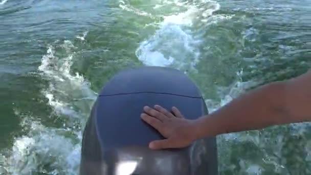 Bootsmotor, menschliche Hand am Motor, während sich das Boot bewegt, schwarzes Meer