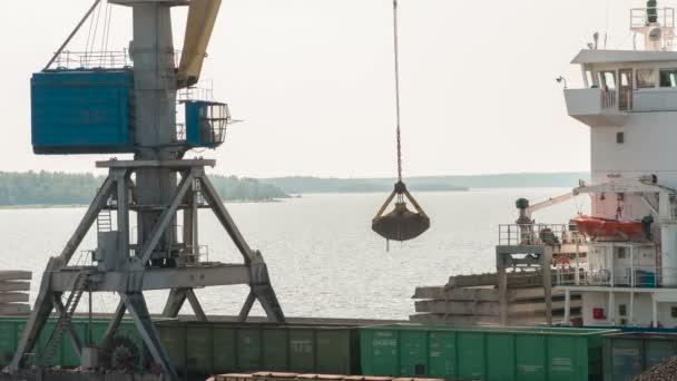 Práce v nákladní přístav. Port marine jeřáb uvolní uhlí od železničních vozů na suché nákladní loď v pozadí v Perském zálivu