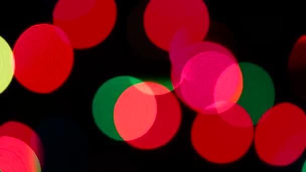 Abstraktní rozmazané světla Bokeh. Barevné blikající indikátory věnec, pomalu se zprava doleva na černém pozadí