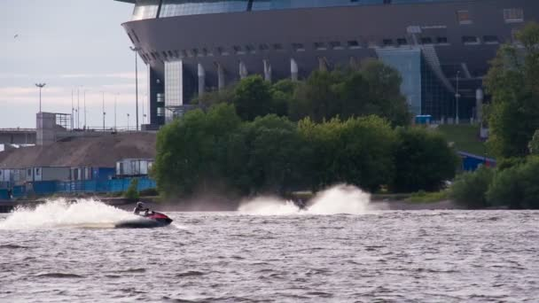 Train Jet Ski in the Water Area. St. Petersburg, Russia, July 2, 2016. New Football Stadium. Two athletes ride a jet ski in the bay on the background being built football stadium for Euro 2018 football