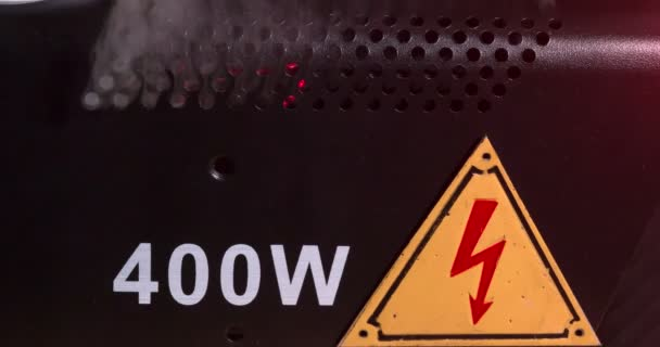Notsituation. schwarzes Gehäuse mit einem Gefahrzeichen für Hochspannung. Durch die Lüftungslöcher steigt Rauch auf. Zeitlupe von 120fps