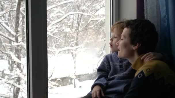 Matka s mladým synem, dívala se z okna. Za oknem sněhová bouře. Maminka a boy nakreslit prstem na zapocené sklo