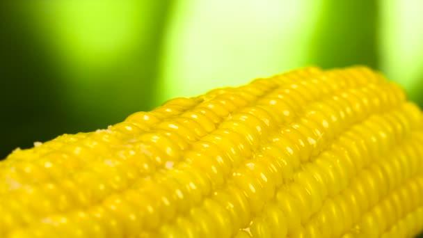 Zrnka soli pomalu spadnout na horké kukuřice vymaštěné máslem. Natočeno s rychlostí 240 snímků za sekundu