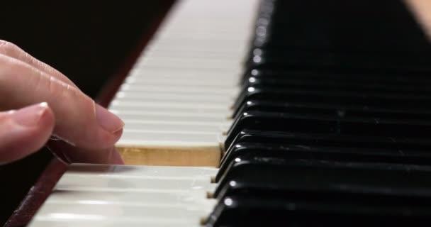 Männliche Finger in Nahaufnahme berühren langsam die Klaviertasten und extrahieren eine einfache Melodie. Gefilmt mit einer Geschwindigkeit von 120fps