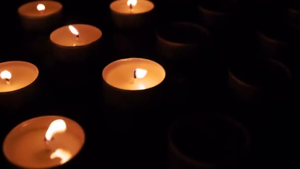 The flame of many candles trembles in the wind. Candles in turn ignite spontaneously