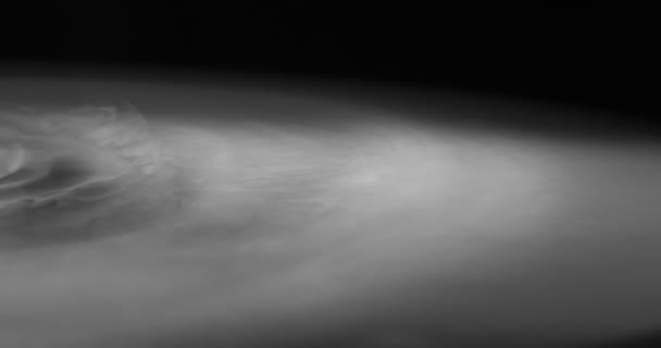 Silný bílý kouř se pomalu rozpouští po černém povrchu
