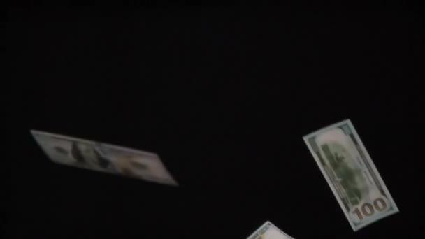 Hundert-Dollar-Scheine schießen in die Höhe. Schleife. Geldwerte im Wert von 100 Dollar in einer großen Anzahl fallen langsam auf schwarzem Hintergrund. Gefilmt mit einer Geschwindigkeit von 240fps