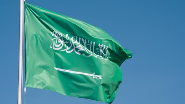 Flag of Saudi Arabia Waves the Wind. The Big State Flag is illuminated by the sun and flutters epically in the wind against the blue sky. Slow Motion 240 fps