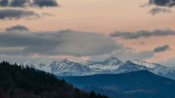 Panoramic view of colorful evening sky over snowy alpine mountains Time lapse