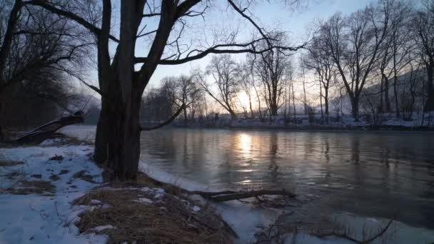 Zimní východ slunce na břehu řeky