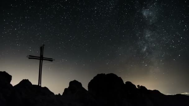 Stars with milky way galaxy moving over cross in top of the mountains Time lapse