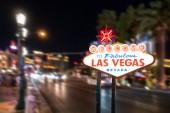 Berühmten Ortsschild von Las Vegas in der Nacht mit Las Vegas Hintergrund unscharf.