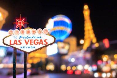 Famous Las Vegas sign at night with Las Vegas Cityscape blur background.